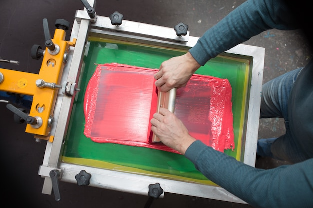 シルクスクリーン印刷。セリグラフィー。色の塗料とファブリック。プラスチゾルペイントとスキージ。