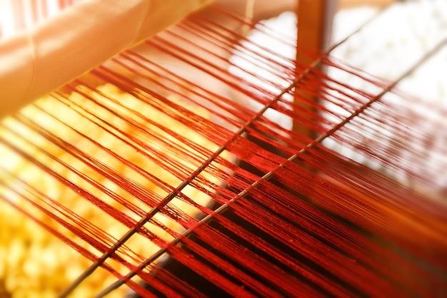 手織り織機のシルク糸ラインは、暖かくて低い室内照明がぼやけており、細部の被写体のコンセプトが低くなっています。