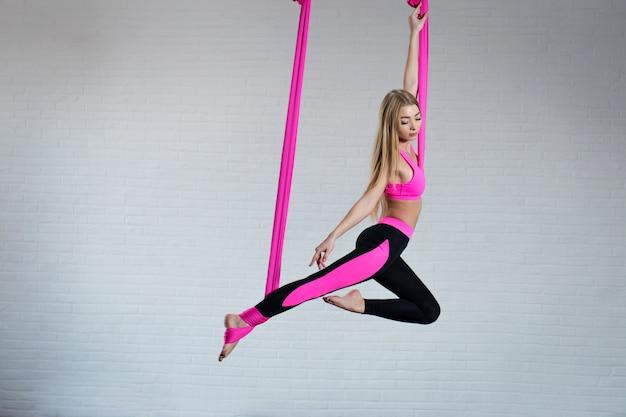 Йога красивой маленькой девочки антигравитационная на розовом silk гамаке пока делающ.