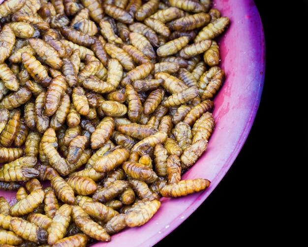 Шелкопряда варить с солью на тарелке уличного рынка
