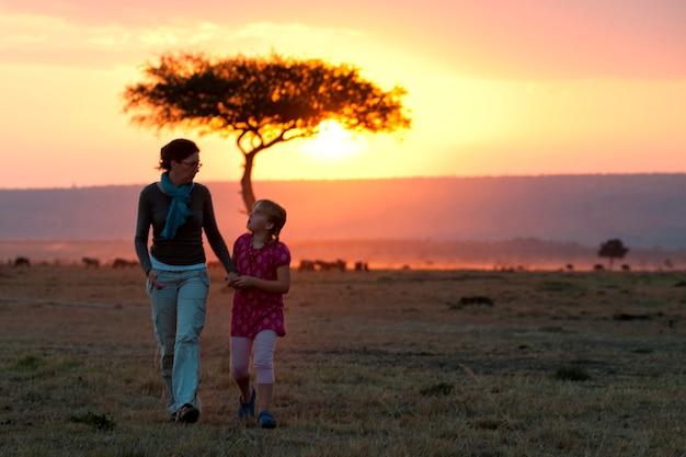 ケニアの日没の空への人々のsillouette