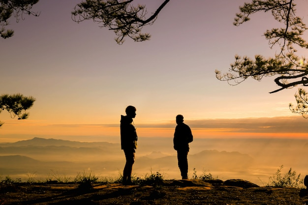 Silluate tow man raise hand up and standing during sunset on top of mountain