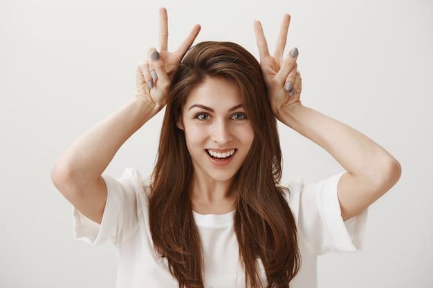 Глупая очаровательная девушка показывает жест кролика и улыбается счастливой