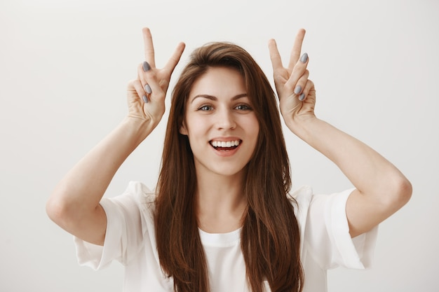 Silly adorable girl showing quotation marks gesture and smiling happy