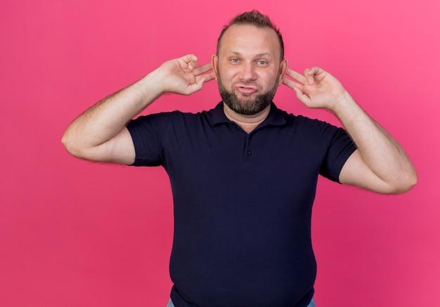 Uomo slavo adulto sciocco che fa le orecchie di scimmia isolate