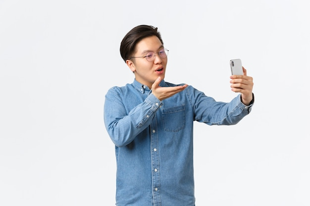 愚かでかわいいアジア人の男が笑って、スマートフォンを使ってガールフレンドと話したり、ビデオ通話やセルフィーを撮ったり、携帯電話のカメラでエアキスを送ったり、白い背景にロマンチックに立ったりします。