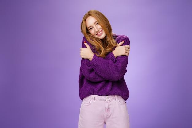 紫色のセーターを着て暖かさを感じながら肩に寄りかかって肩に寄りかかっている愚かでかわいいのんきな赤毛の女性は、紫色の壁の上の居心地の良いリラックスした雰囲気の中で広く笑っています。