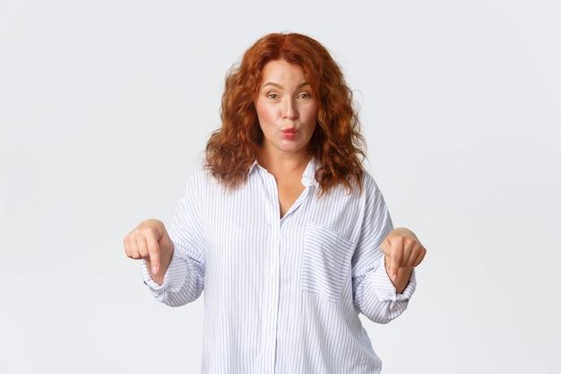 愚かでかわいい中年の赤毛の女性は、指を下に向けて、特別オファーのバナーを表示し、発表を行い、白い背景に立って、ふくれっ面とヒントを与えます。