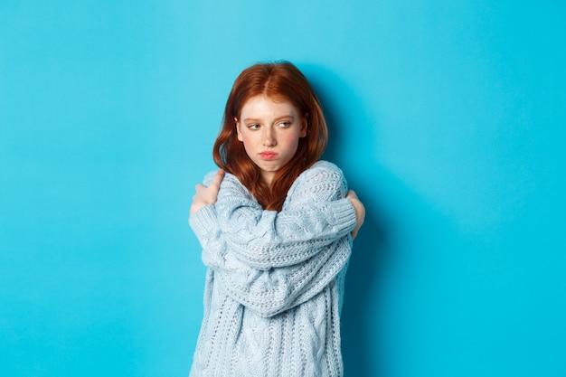 어리 석고 귀여운 빨간 머리 소녀 주름 입술과 기분을 상하게하고, 자신을 껴안고 멀리보고, 파란색 배경 위에 서서 불쾌하고 찡그리고 화가납니다.