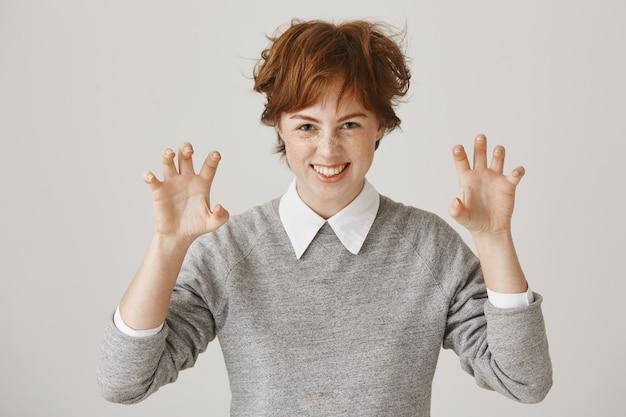 짧은 머리가 흰 벽에 포즈를 취하는 어리 석고 재미있는 빨간 머리 소녀