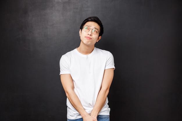 Глупый и застенчивый мечтательный милый азиатский гей вздохнул и задумался