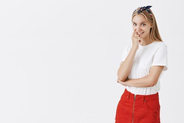 白い壁にポーズをとって愚かな美しい若いブロンドの女の子