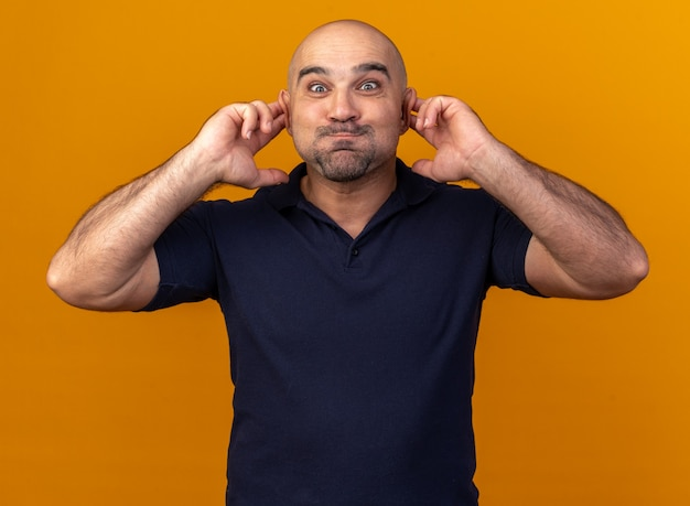 Silly casual middle-aged man  puffing cheeks making monkey ears isolated on orange wall