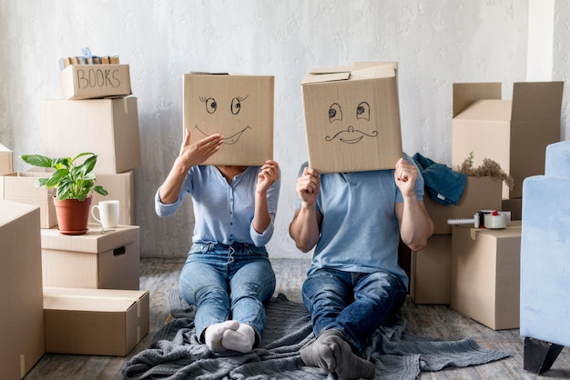 Silly couple at home on moving day with boxes over head