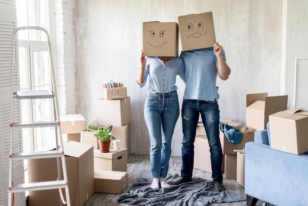 Глупая пара позирует с коробками над головами в день отъезда