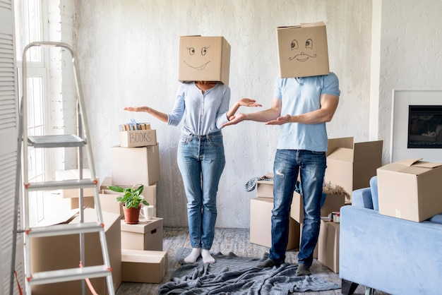Silly couple with boxes over heads on moving out day
