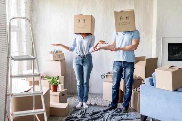 Глупая пара с коробками над головами в день отъезда