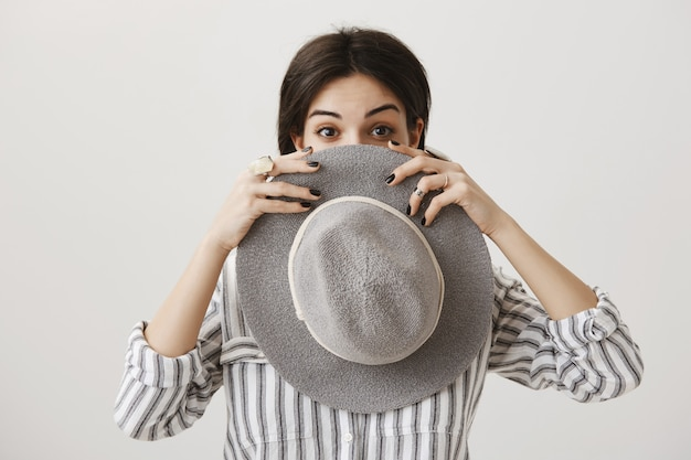 帽子の後ろに顔を隠して覗く愚かなかわいいブルネットの女性