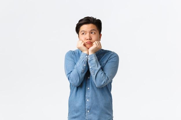 Sciocco e carino ragazzo asiatico sognante che guarda nell'angolo in alto a sinistra con il viso desideroso, appoggiato ai palmi timidi, pensando a qualcosa che desidera, sentendosi annoiato o triste, in piedi su sfondo bianco.