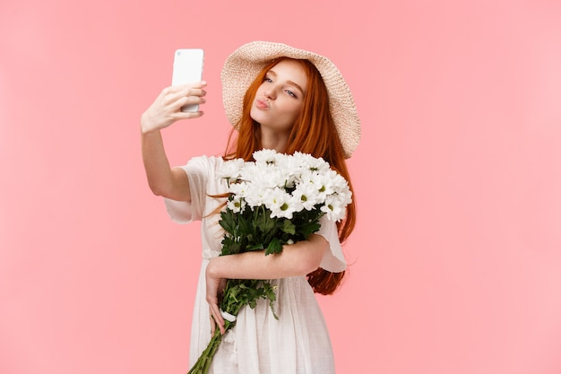 Silly and cute, feminine girl blogger taking selfie with bouquet flowers boyfriend brought, holding smartphone folding lips in air kiss, posing for perfect sensual shot, stand pink