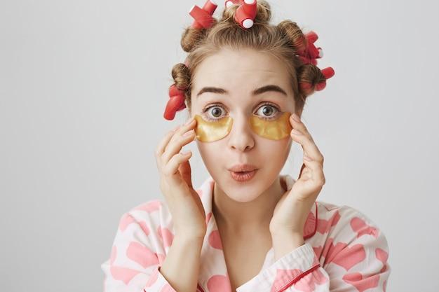 Stupida ragazza carina in bigodini e indumenti da notte applica bende sugli occhi