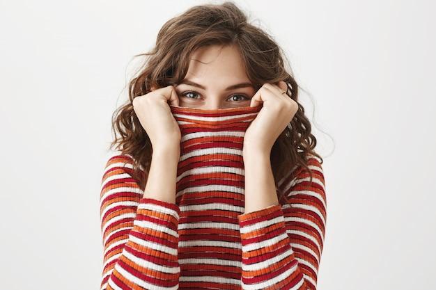 Глупая милая девушка прячется в свитер, улыбаясь глазами