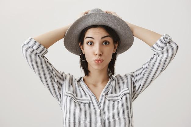 休暇の準備ができて、帽子をかぶってふくれっている愚かなかわいい女の子