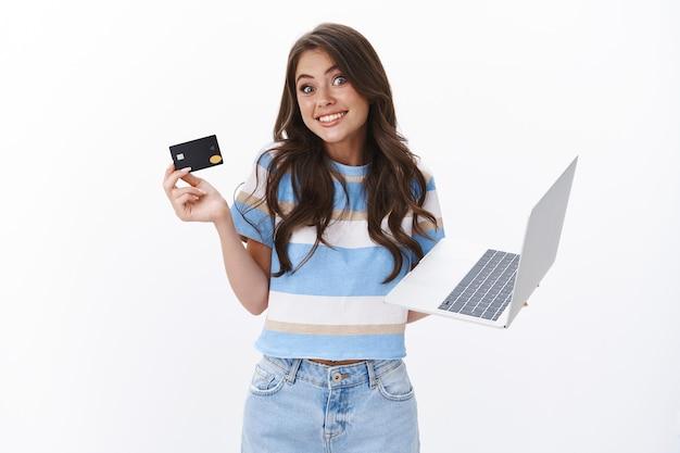 Глупая милая счастливая женщина, радостно улыбаясь, пожимая плечами и глядя в камеру, объясняет, как легко использовать онлайн-банкинг, держать ноутбук и кредитную карту, рекомендовать покупки в интернете