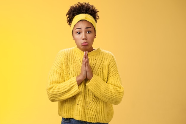 Глупая милая жалкая молодая афро-американская дочь-подросток, просящая карманные деньги, пойти в поездку, нажать ладони, молясь, помолиться, попросить о помощи, сделать грустное надутое жалкое выражение, стоя на желтом фоне.