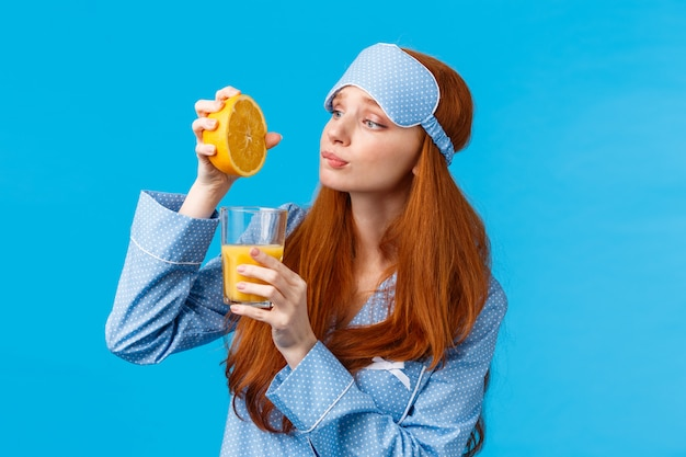Silly and cute redhead caucasian girl in sleep mask and nightwear, looking with hopeful and eager expression, like eating fruits, squeeze orange in glass to make breakfast juice, blue wall