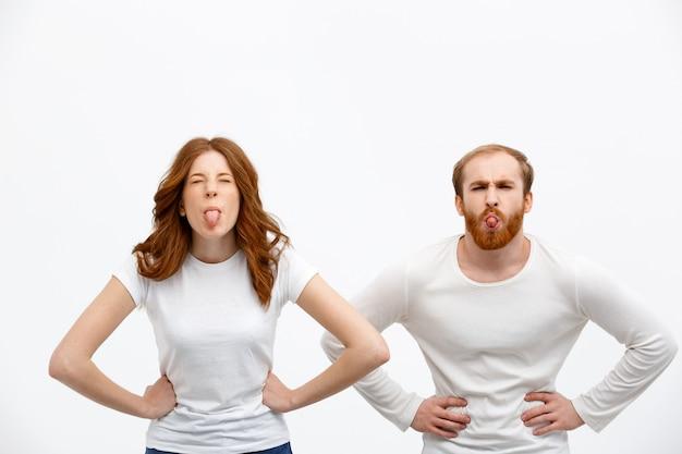 舌を示す愚かなかわいい赤毛のカップル