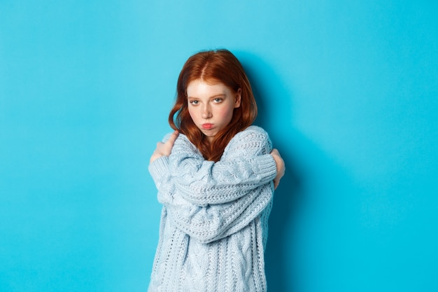 Silly and cute redhead girl pucker lips and looking offended, comforting herself by cuddling, embracing body and staring at camera defensive, blue background.