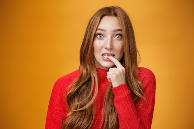 Silly, cute redhead woman making innocent oops expression holding finger on lip and looking scared with questioned expression at camera making mistake and trying get away of troubles with flirty gaze