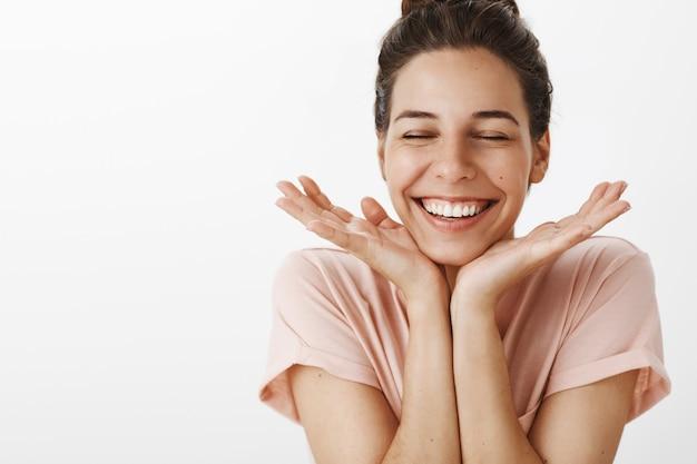 白い壁にポーズをとって愚かなかわいい笑顔の女の子