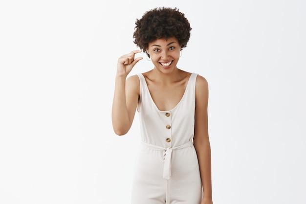 白い壁にポーズをとる愚かなかわいいスタイリッシュな女の子