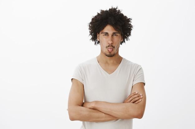 Uomo sciocco dalla pelle scura che fa una smorfia e mostra la lingua per l'avversione