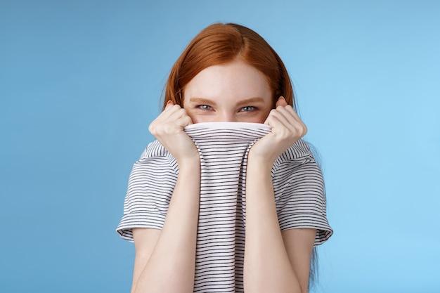 Sciocco flirty divertito attraente ragazza rossa giocosa nascondendo il viso tirando la testa t-shirt socchiudendo gli occhi misteriosamente ridacchiando ridendo speranza travestimento scherzo amico in piedi sfondo blu