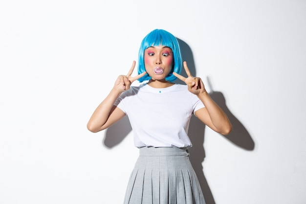 Silly and funny asian girl blowing bubble gum, showing peace gestures, standing in blue short wig