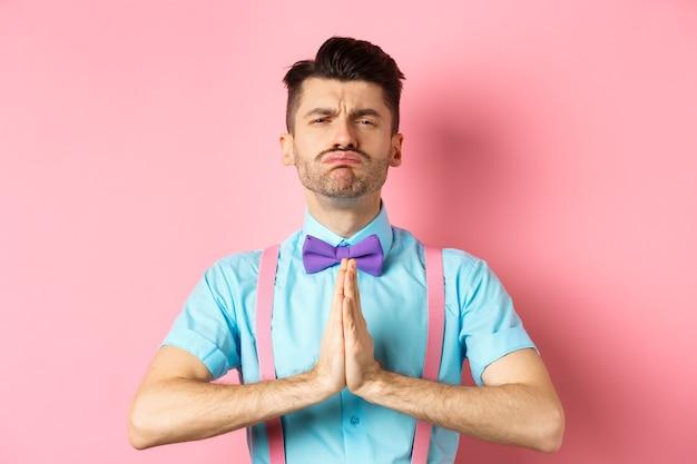 ピンクの背景に手を一緒に押して立って、懇願する顔を作り、懇願し、助けを求める愚かな男。コピースペース