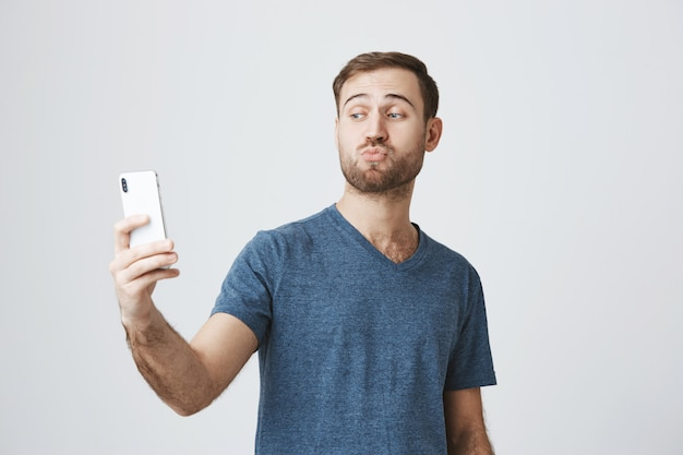 Silly handsome guy taking selfie on smartphone, pouting