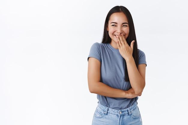 어리석은 끔찍하고 흉측한 아시아 여성 대학생이 누군가가 속는 것을 지켜보며 구석에서 장난을 치고 킥킥거리며, 왼쪽을 바라보고, 손으로 웃는 입을 가리고, 비밀리에 킬킬대는 흰 벽