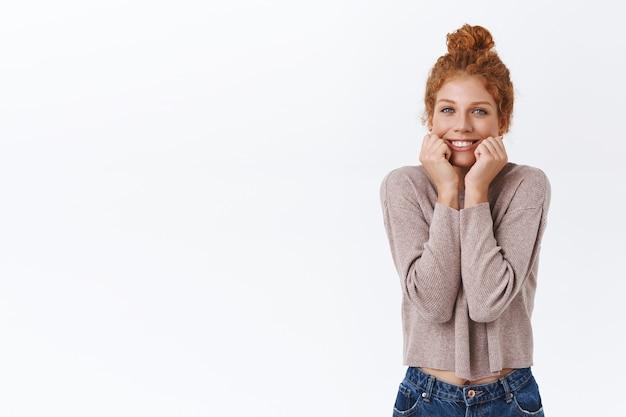 곱슬머리를 가진 어리석고 사랑스러운 백인 빨간 머리 여성, 하얀 아름다운 미소, 뺨을 쥐어짜고 애정, 감탄, 행복으로 카메라를 응시하는 흰색 벽