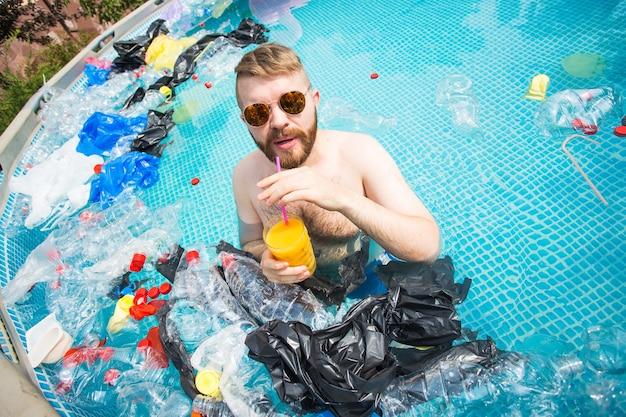 愚かな男は、汚染されたプールで泳いで楽しんでいます。ボトルやビニール袋が近くに浮いています。