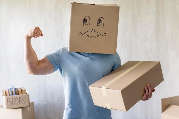 Глупый человек с коробкой над головой показывает бицепс в день переезда