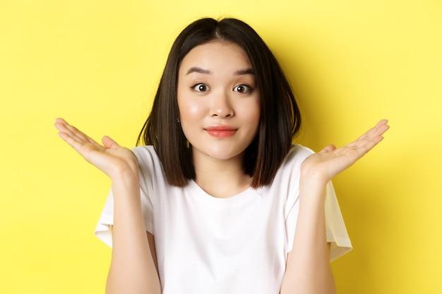 愚かな間違い。黄色の背景の上に立って、申し訳ありませんが、肩をすくめるとおっとの表情で笑って、かわいいアジアの女の子のクローズアップ