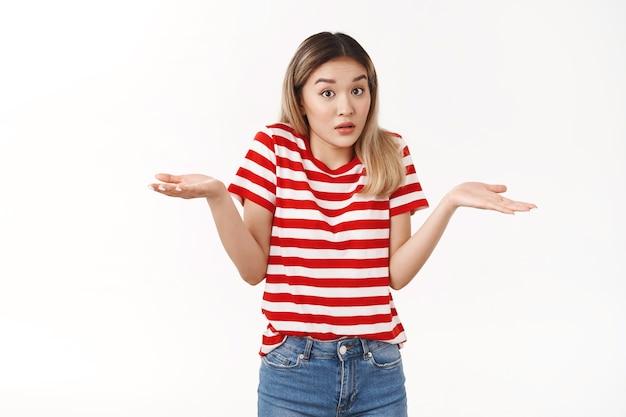Глупая озадаченная азиатская белокурая студентка пожимает плечами, раскинув руки в стороны, не может ответить понятия не имею, поднимать брови, не подозревая, озадачена, сомневаюсь, не уверена в личном мнении