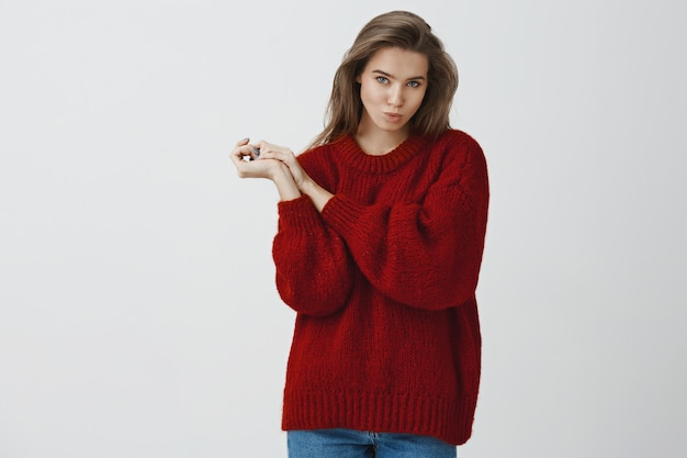 Silly and playful sexy woman in red loose warm sweater making flirty glances  folding lips kissing sending air mwah holding palms pressed together cute, seducing with gazes over white wall
