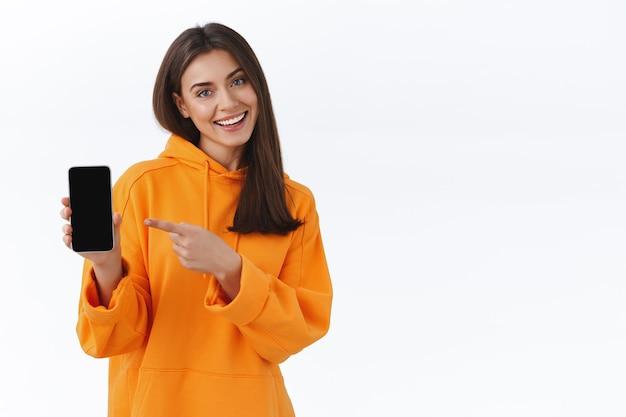 휴대폰을 들고 스마트폰 디스플레이를 가리키며 새로운 응용 프로그램을 소개하고 멋진 게임에서 새로운 점수를 자랑하고 흰 벽에 서 있는 유쾌하고 친근한 갈색 머리 소녀