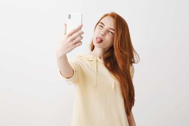 혀를 보여주는 어리석은 빨강 머리 소녀와 셀카 복용