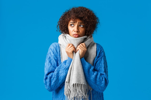 Silly and sad, gloomy african-american girl looking outside windy snowy weather winter, wrap neck with warm scarf, tremble from cold feeling discomfort from low tempreture at home, blue